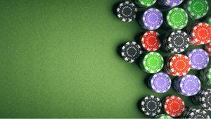 Casino-poker-chips-on-green-felt-background