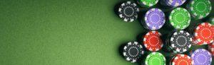 cropped-Casino-poker-chips-on-green-felt-background.jpg